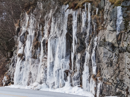 Frozen waterfall plunging from a steep rock cliff beside the road Banque d'images