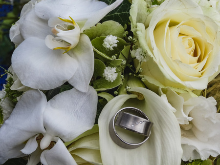 Two silver wedding rings with gems on creamy roses wedding bouquet close up