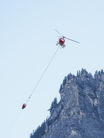 Fire helicopter with water tank in the air near kandersteg switzerland