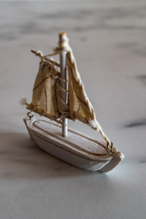 little white sailboat decoration on a marble plate closeup