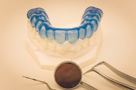 Detailed close up of dental instrument and blue denture or teethe protection on a table, dentistry Stock Photo