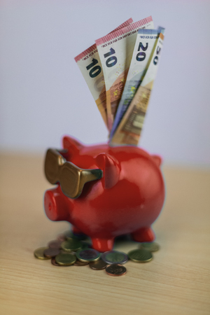 cool red piggy bank with golden glasses with euro coins and note isolated on wooden table, treasure