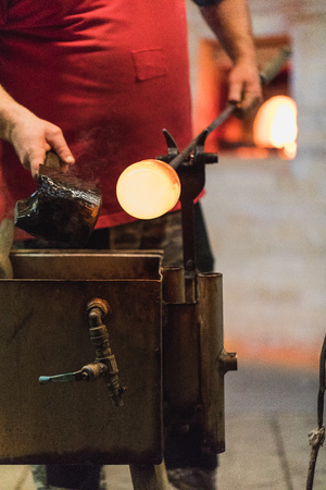 glass blower carefully forming hot glass to a decorative vase, germany