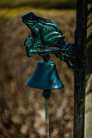 green frog figure with a bell on a garden door in germany Stok Fotoğraf