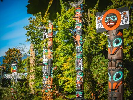 Colorful indian totems in stanley park vancouver canada summer Stock Photo