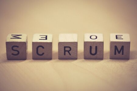 wooden cubes showing the word scrum on a table, office