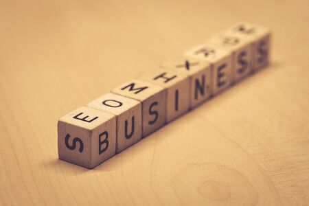 wooden cubes showing the word business on a table, office Imagens