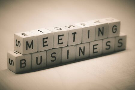 wooden cubes showing the word business meeting on a table, office
