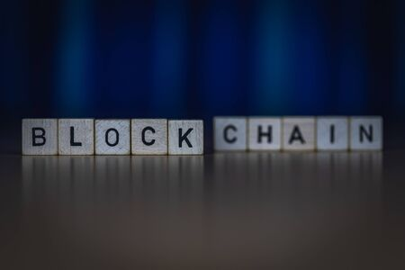 macro shot of wooden cubes on a table showing the word BLOCKCHAIN, Business Banque d'images - 131937669