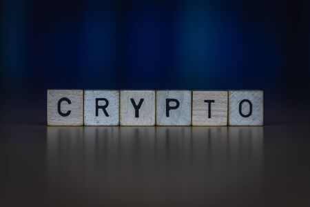 macro shot of wooden cubes on a table showing the word CRYPTO, Business