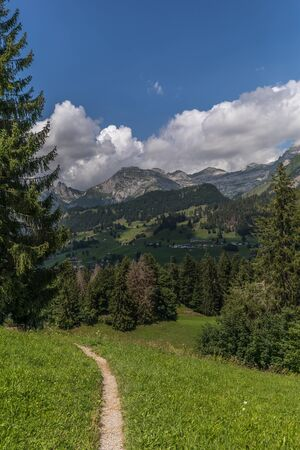 Hiking through swiss alps on a sunny day with blue sky near toggenburg, gamsalp Stock Photo - 128611592