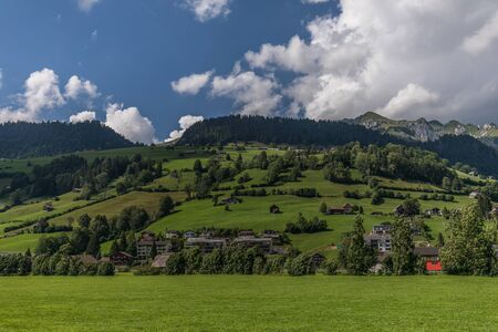 Hiking through swiss alps on a sunny day with blue sky near toggenburg, gamsalp Stock Photo - 128611543