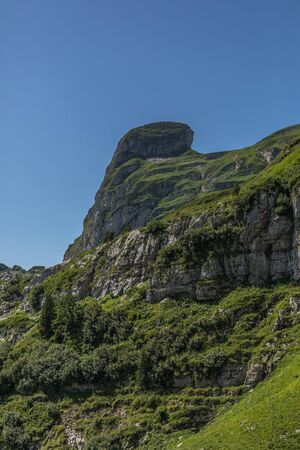Hiking through swiss alps on a sunny day with blue sky near toggenburg, gamsalp Stock Photo - 128611566