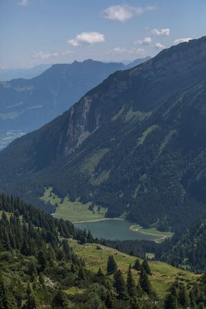 Hiking through swiss alps on a sunny day with blue sky near toggenburg, gamsalp Stock Photo - 128611575