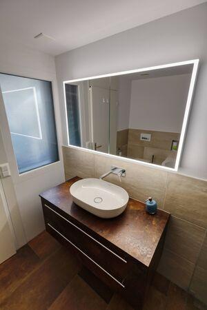Interior of a modern bathroom with brown furniture, washroom Archivio Fotografico
