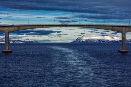 Wake after ship with bridge in background in norway in winter, europe Imagens