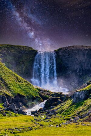 svodufoss waterfall under night galaxy sky in iceland, summer Banco de Imagens