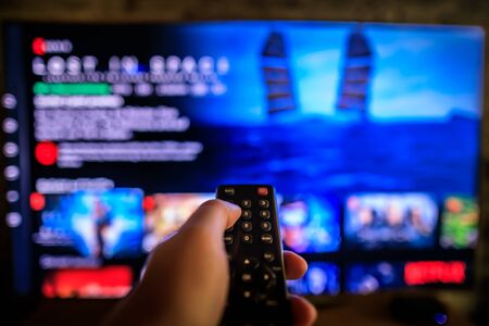 Video on demand screen with remote control in hand, streaming