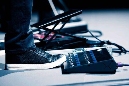 Guitar player in sneakers stomp overdrive pedal, studio Imagens