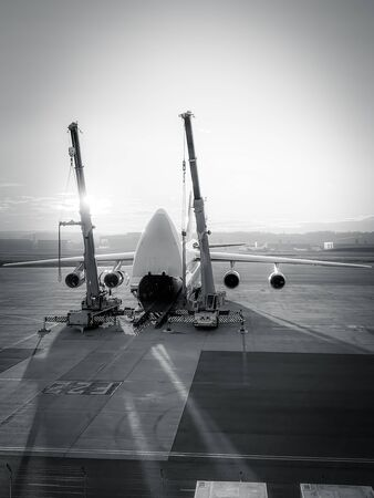 antonov an-124 on the ground with wide open freight room and two cranes beside, fuel stop