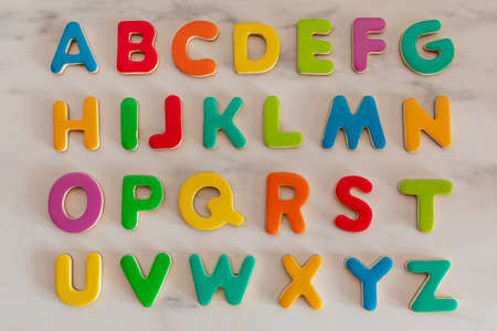 Colorful letters on marble background, alphabetical order, top view Archivio Fotografico
