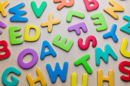 colorful mixed letters pile on a wooden table, top view Archivio Fotografico