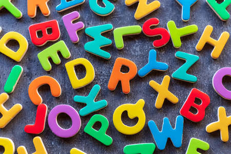 colorful mixed letters pile on a granite table, top view