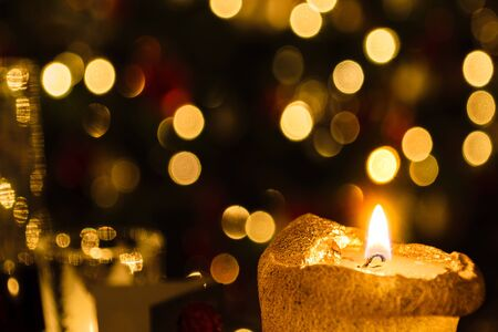 Christmas candle against colorful shiny blur background