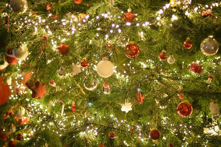 Closeup of Christmastree decorations on tree - shiny light