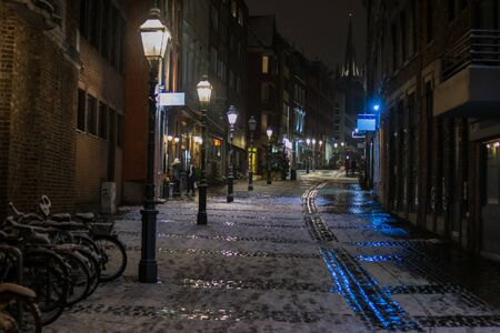 Snowy empty street at night in Aachen, Germany - lights and reflections Banque d'images