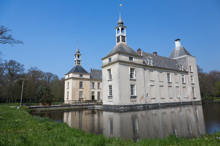 rebuild: Warmond, The  Netherlands - april 24, 2015 - Huys te Warmont is an historic building surrounded by a moat with two towers and a clock. build in the 12th century and rebuild in the 18th century
