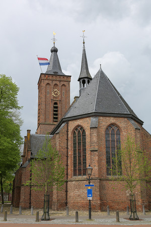 wind vane: Dutch flag waving in the wind, during liberation day, from a church tower over the village of Scherpenzeel, The Netherlands.Photo taken on May 05, 2015