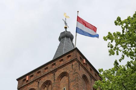 Nederlandse vlag wapperen in de wind, tijdens de bevrijding dag, van een kerktoren over het dorp van Scherpenzeel, The Netherlands.Photo taken on 5 mei 2015