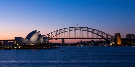 cahill: SYDNEY, AUSTRALIA - OCTOBER 14, 2016: Two of Sydneys famous icons, the Sydney Opera House and Sydney Harbour Bridge lit up at dusk after a vivid sunset, the sky still aglow with colour.