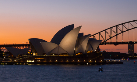 SYDNEY, AUSTRALIA - OCTOBER 14, 2016: Two of Sydneys famous icons, the Sydney Opera House and Sydney Harbour Bridge lit up at dusk after a vivid sunset, the sky still aglow with colour.