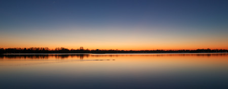plassen: Cold winter sunset at Reeuwijk lake district under a blue and orange sky, panorama