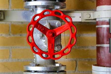 under control: Industrial red valve and pipeline