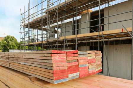 Stapel houten studs en steiger met tijdelijke daken op een bouwplaats Stockfoto