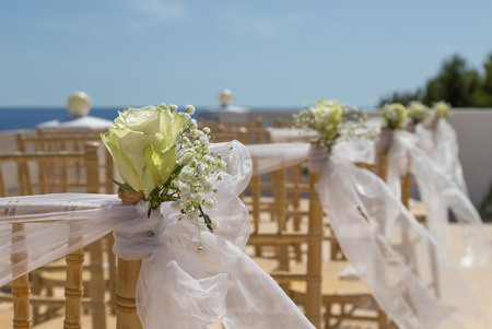 White flowers on chairs before a wedding ceremony at a venue on the beach