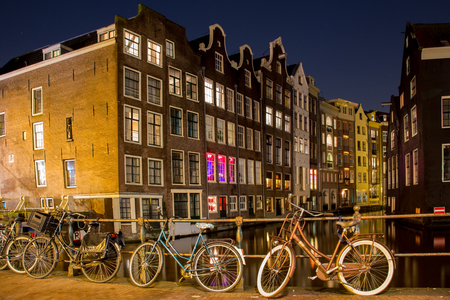 Amsterdam bikes parked near the canal and houses at night