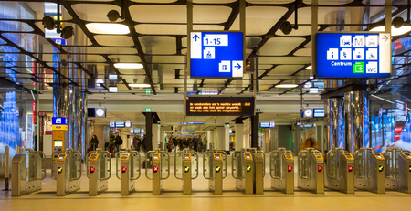 AMSTERDAM, THE NETHERLANDS - January 05, 2018:  Ticketing gates at the entrance of Amsterdam central station with blurred passengers, panoramic view Editorial