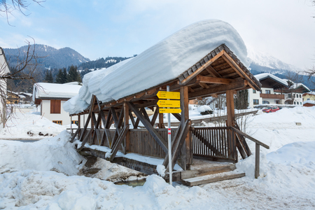 Snow covered wooden bridge in winter in the Austrian town of Kleinarl.