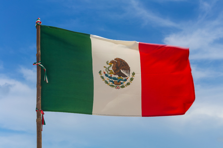 Mexican flag waving in the wind against a blue sky