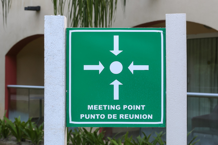 Meeting point sign where to meet in case of an emergency, dual language, English and Spanish.