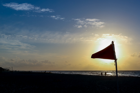 Silhouetted Safety flag for swimming during Sunset at the beach