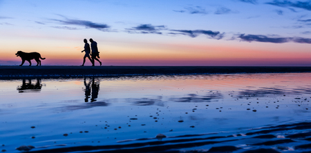 Silhouetted couple walking on the beach at sunset, Noordwijk, the Netherlands - with copy space.Photo duties on July 31, 2018