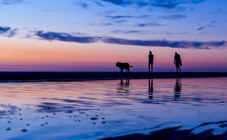 Silhouetted couple walking on the beach at the water, Noordwijk, the Netherlands - with copy space.Photo duties on July 31, 2018 版權商用圖片
