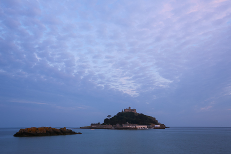 St. Michaels Mount castle is located on the top of an granitic-rock island near Marazion, Cornwall, England. Visitors can walk to the island during low tide. Sunset and clouds.