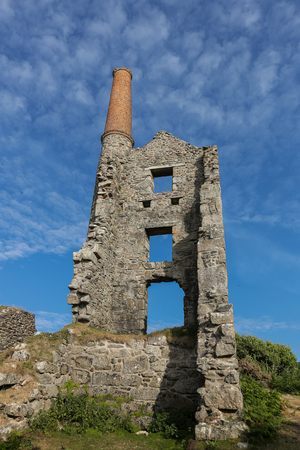 The ruins of Carn Galver Mine on the coast at a sunny day near Penwith Cornwall England. The engine house was used during tin mining and is now owned by the National Trust.