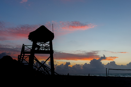 Beach sunrise with silhouetted lifeguard tower at Playa del Carmen, Mexico